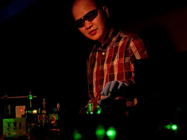 Brown University physicist Cuong Dang directs a green laser onto a film of colloidal quantum dots, which reemit RGB light.