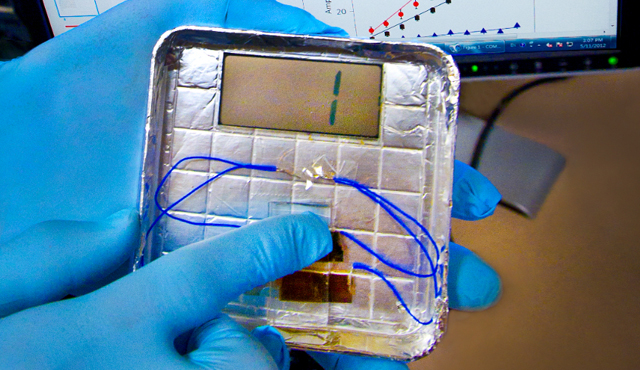 Pressing a virus-filled device can generate power. (The gloves  protect the virus, which only infects bacteria, from us.)