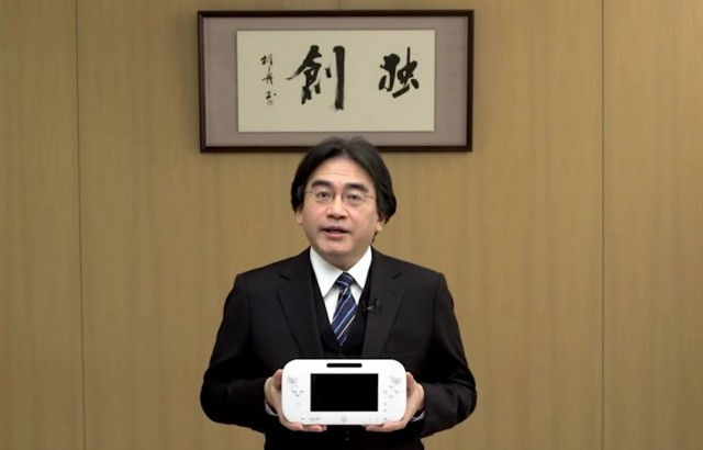 Nintendo President Satoru Iwata holds the Wii U GamePad.