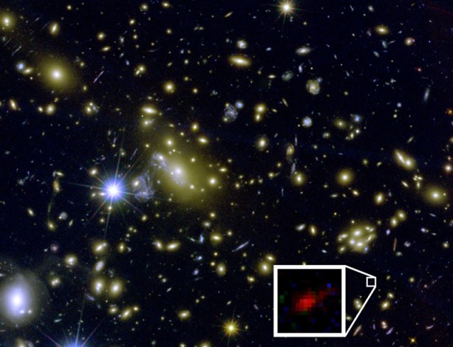The inset shows light from a possible galaxy, emitted 490 million years after the Big Bang. The galaxy's light was magnified by the galaxy cluster that dominates the image.