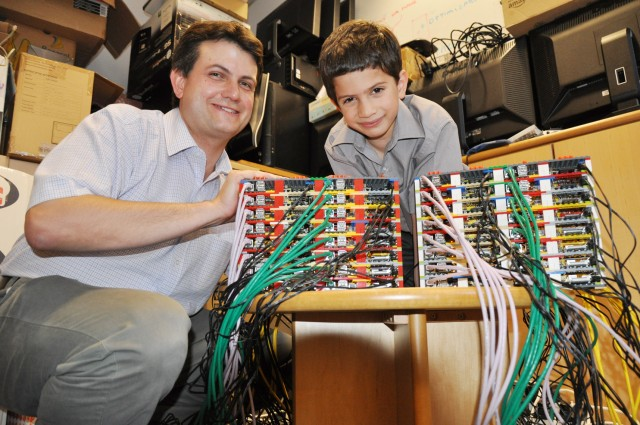 "Professor Simon Cox of the University of Southhampton with his son and system racking consultant, James, show off their Raspberry Pi-based ""supercomputer."""