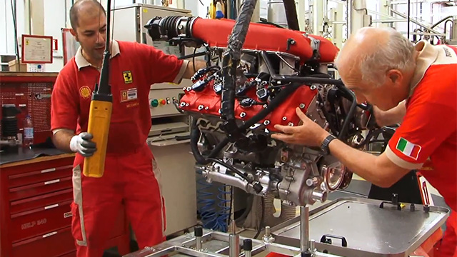 Workers assemble the engine for a Ferrari 458 Italia, which uses direct injection.