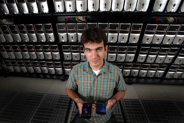 Sandia researcher David Fritz standing in front of a cluster of Android virtual machines, holding two Galaxy Nexus phones.