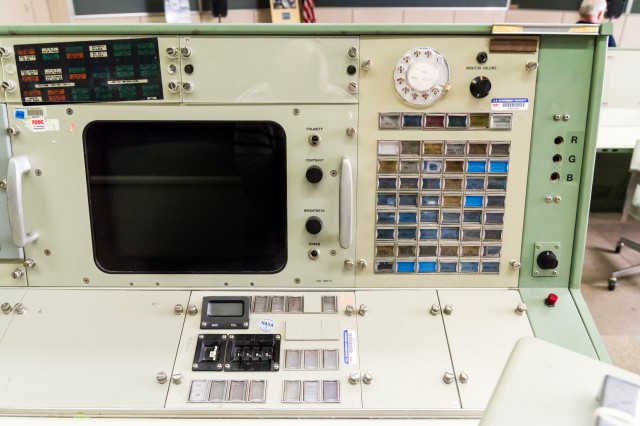 The right half of Public Affairs Office console is typical of most of the consoles today, with a PABX communications panel and a display selection panel below a pair of screens (the second screen is off-frame to the left).
