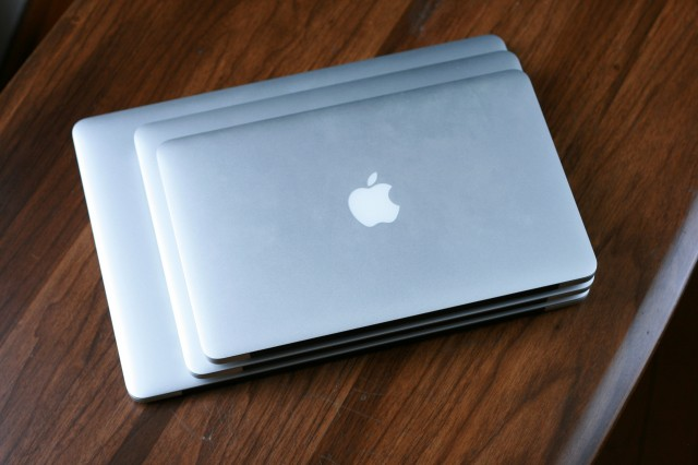 "A stack of MacBooks, with a 15"" Retina MacBook Pro on the bottom, a 13"" Retina MacBook Pro in the middle, and an 11"" MacBook Air on top."