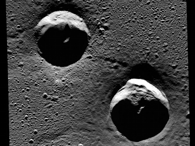 Two craters in the Goethe basin near the planet Mercury's north pole. Portions of these craters are permanently shadowed, meaning they are never subjected to sunlight. Similar craters have recently been found to contain water ice and organic materials.