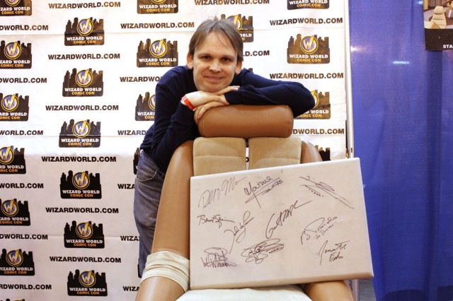 Huston Huddleston poses with the signed panel on one of the chairs.