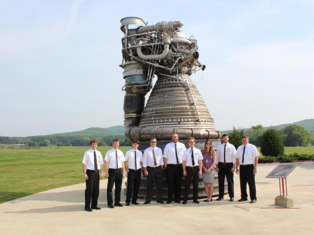 Modern engineers in 1960s engineer dress cluster around an F-1. The Russian RD-170 produced more power but isn't really a single engine.