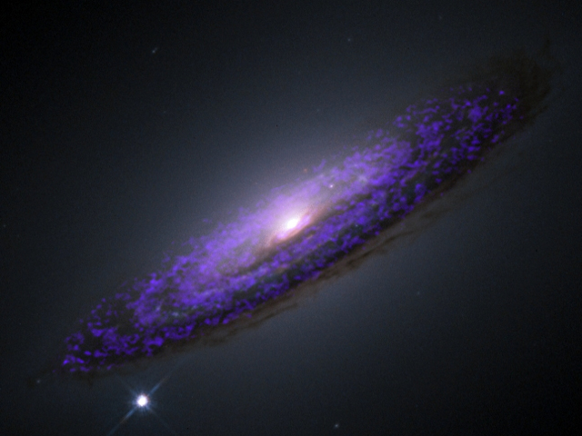 A Hubble Space Telescope image of the galaxy NGC 4526, overlaid with submillimeter observations (shown here in purple). The submillimeter light shows the presence of molecular gas, which could assist in estimating the mass of the galaxy's central black hole.