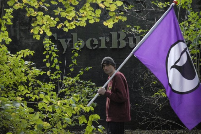 Sven Olaf Kamphuis waving the Pirate Party flag in front of CyberBunker's nuclear bunker.