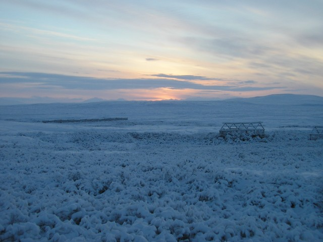 A greenhouse in winter, with the rest of the tundra frozen around it.