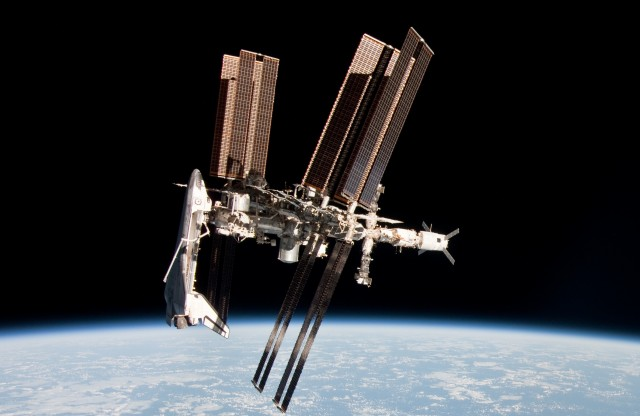 Transverse view of ISS (with <em>Endeavour</em> docked). Integrated Truss Structure visible in foreground, with P6 segment closest to camera.