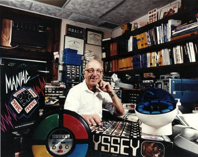 Ralph Baer posing in his personal lab with some of his most famous products.