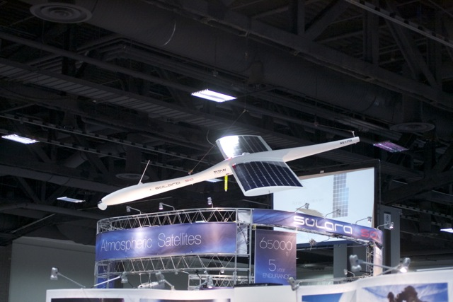 "A model of the Solara 50, Titan Aerospace's commercial ""atmospheric satellite,"" hangs above the company's booth at the AUVSI Unmanned Systems conference in 2013."