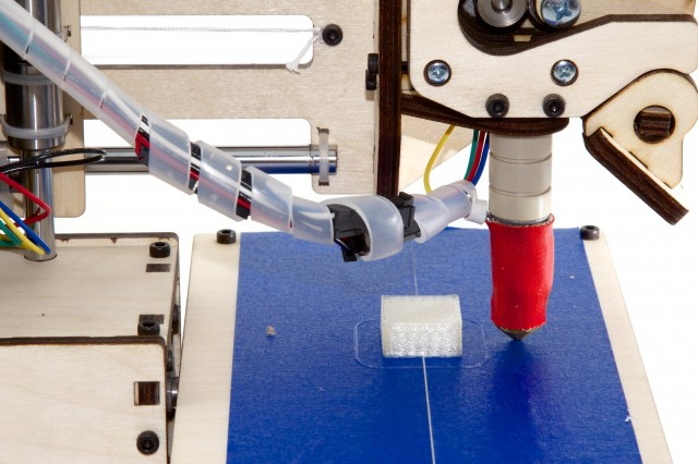 Close-up of the Printrbot's bed. The extruder tip is wrapped in red because it gets hot while printing.