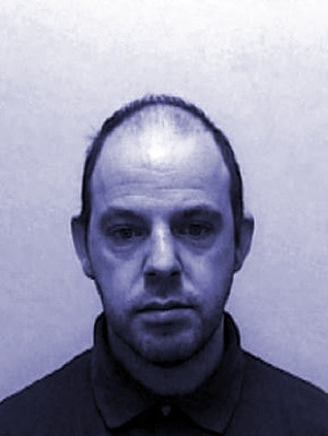 The UK booking photo for Delwyn Savigar—DAS—the leader of The Cache. After his arrest, DNA evidence tied him to several unsolved sexual assaults.