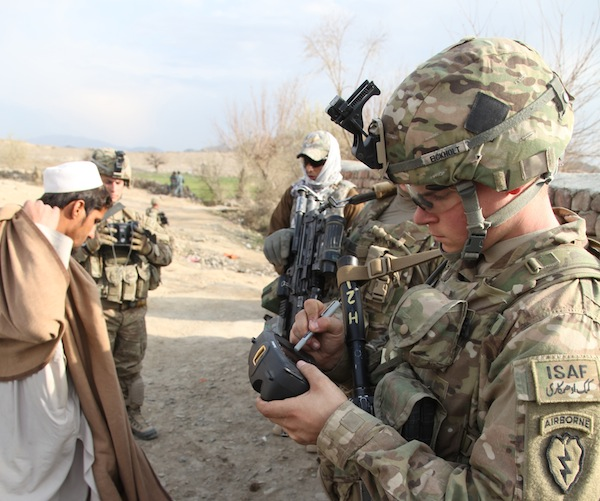A soldier uses a biometric data capture device on patrol in Afghanistan. DARPA's CBMEN project aims to let soldiers share biometric data, images, and other tactical information locally without needing to upload it to a server.