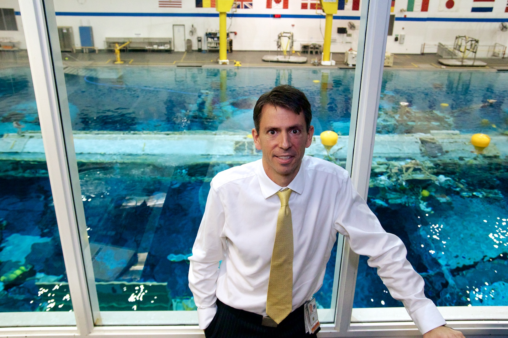 "NASA EVA Task Group manager Zeb Scoville, standing in one of the test coordinator control rooms at the <a href=""http://arstechnica.com/science/2013/03/swimming-with-spacemen/"">Neutral Buoyancy Laboratory</a>. Visible behind him is the NBL pool."