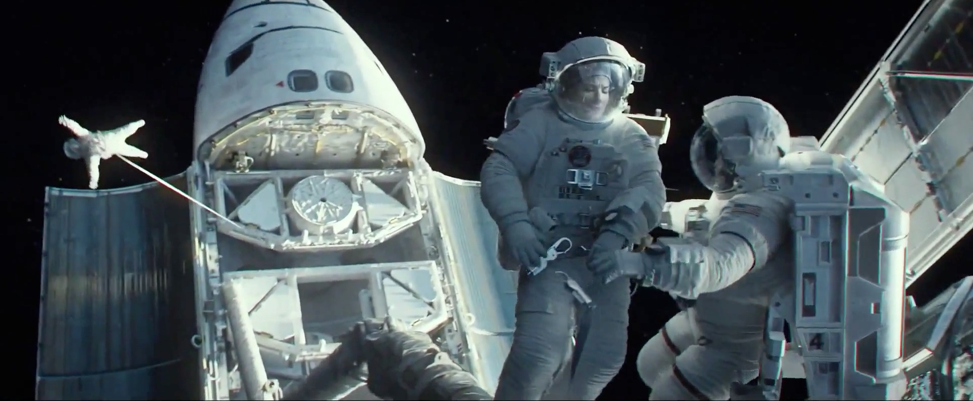 Clooney assists Bullock, while in the background another hapless astronaut is hit by debris.