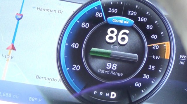 "What the driver sees while in motion. The central round display shows forward speed and energy usage, as well as the ""rated"" range available. Visible to the left is the active navigation system showing turn-by-turn directions."