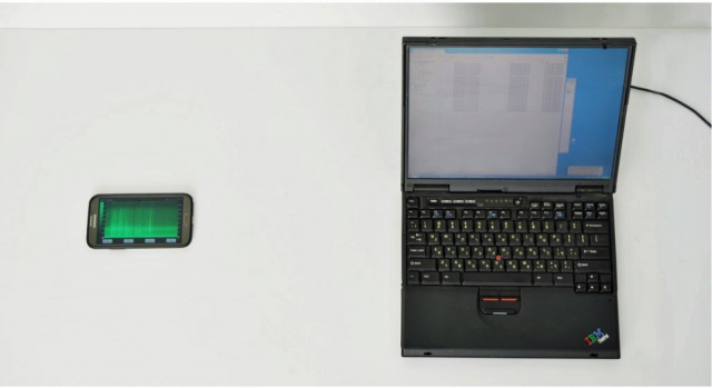 Physical setup of a key recovery attack. A mobile phone (Samsung Note II) is placed 30 cm (nearly 12 inches) from a target laptop. The phone's internal microphone points toward the laptop's fan vents. Full key extraction is possible in this configuration and distance.