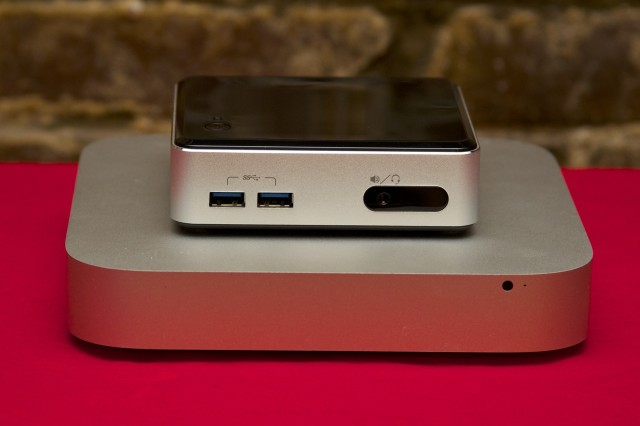 The NUC dwarfed by a Mac Mini. The Mini has an integrated power supply while the NUC's is external, but the total volume of the NUC is still smaller.