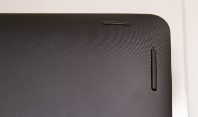 The lid is a black textured plastic. The power button and volume rocker are on the lid toward the top-right edge (or top-left, if you're looking at the screen).