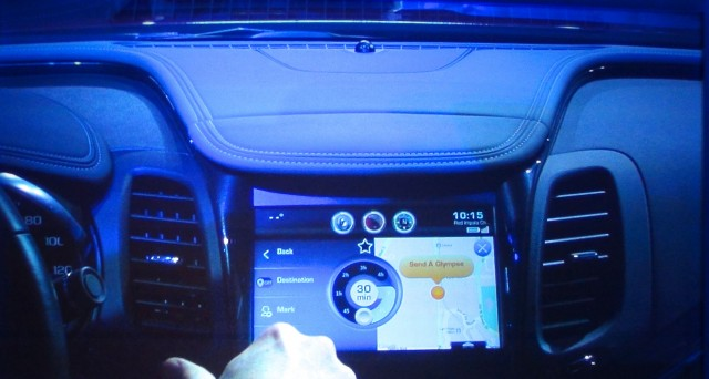 A GM employee demonstrates the interface to Glympse in a 2015 Chevy Malibu onstage at GM's CES event.