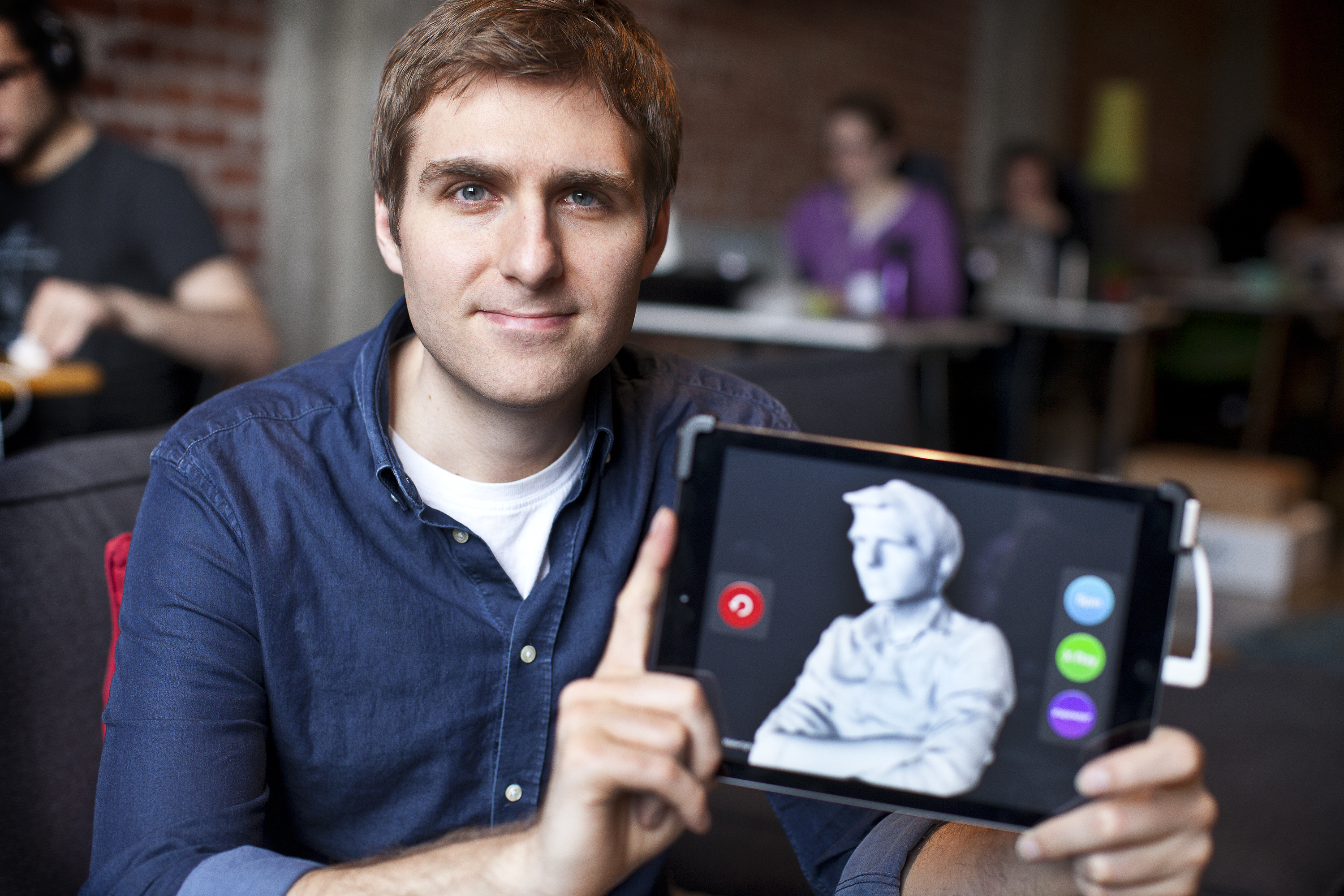 Jeff Powers, CEO of Occipital, sits holding an iPad with a 3D image of himself that was scanned earlier.