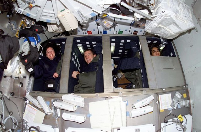 STS-107 mission specialists Laurel B. Clark, Rick D. Husband, and Kalpana Chawla relaxing in their bunks on <em>Columbia</em>'s middeck.