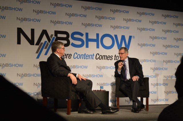 NAB President and CEO Gordon Smith listens to FCC Chairman Tom Wheeler on stage in Las Vegas.