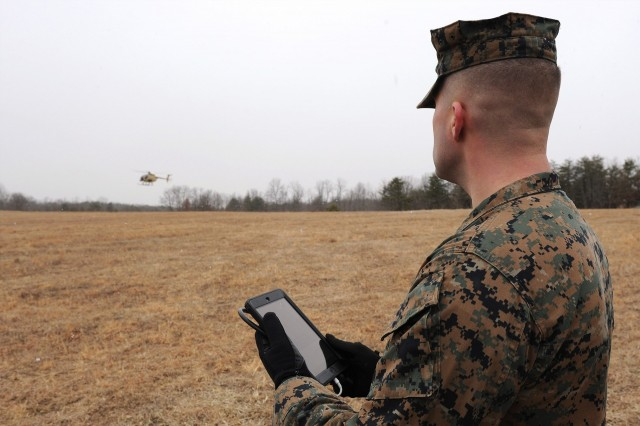 Lance Cpl. Cody Barss using a handheld tablet to request resupply
