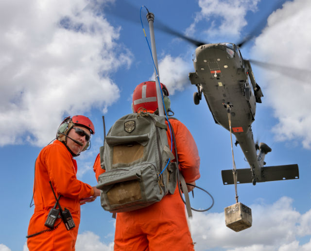 A demonstration by Sikorsky and the Army Research, Development, and Engineering Command of the Optional Pilot Black Hawk near West Palm Beach, Florida, on March 11, 2014. The man with the backpack is controlling the helicopter in hover.