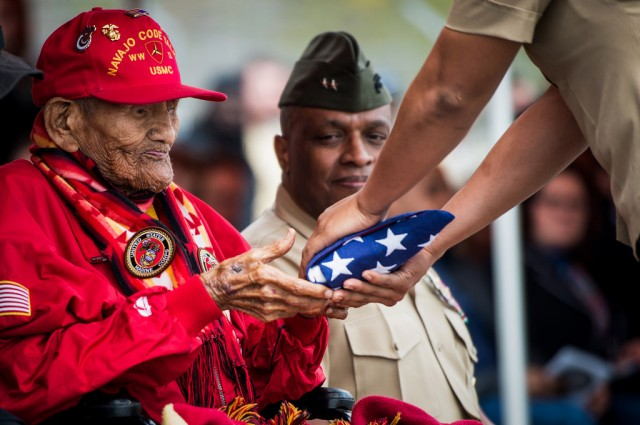 US Marine Corps Cpl. Chester Nez receives an American flag from Pfc. Tiffany Boyd, at Code Talker Hall, Marine Corps Base Quantico, VA, April 4, 2014. The flag was flown over the Marine Corps War Memorial, on the first day of spring, in honor of Cpl. Nez's attendance at the Platoon 382 Hall rededication. Cpl. Nez was the last of the original 29 Navajo Code Talkers of World War II.