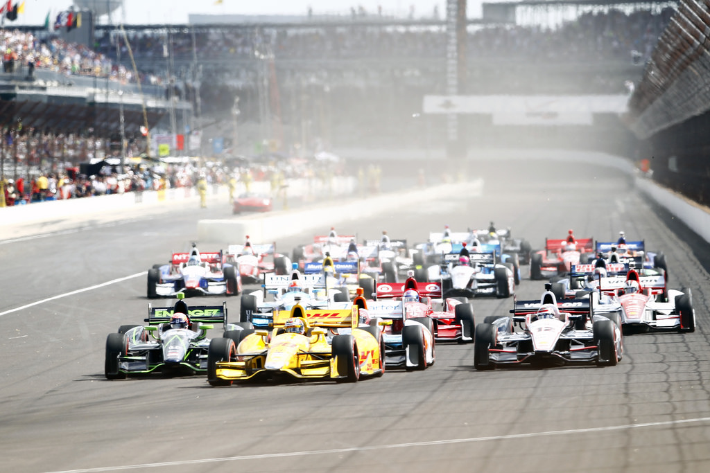A field of DW12 IndyCars head for turn 1 at the start of the 2014 Grand Prix of Indianapolis, the first time IndyCars have run on the road course at the hundred-year-old track.