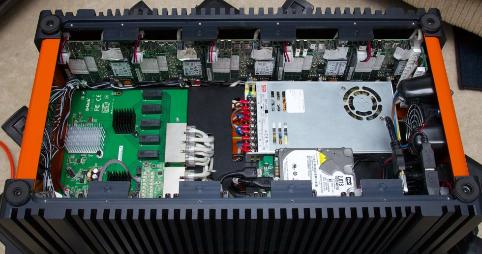 Looking down into the Orange Box. The ten naked NUCs are vertically mounted to the walls, while the central cavity includes a power supply, gigabit Ethernet switch, and shared storage.
