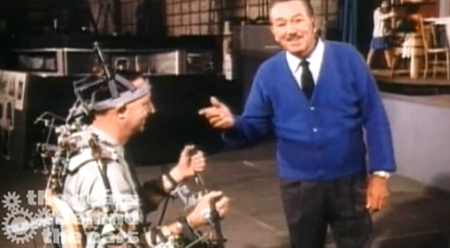 Disney engineer Wathel Rogers in the control harness, on the left, used for programming animatronic characters' movements, with Walt Disney on the right.