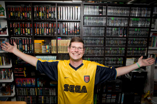 Thomasson poses with just a few of his 11,000 video games.