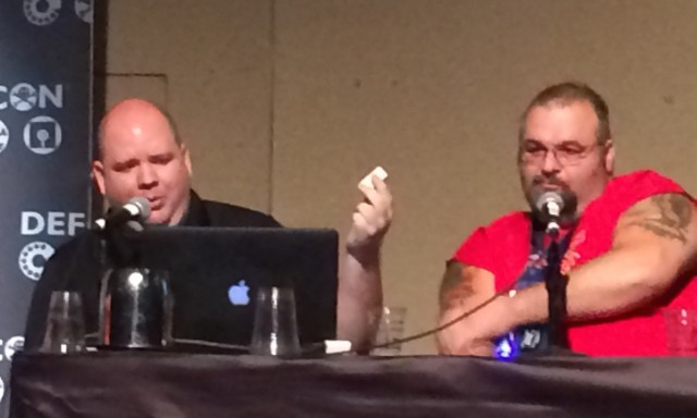 Ryan Lackey (left) holds up a prototype PORTAL travel router during his Def Con presentation with Marc Rogers (right).