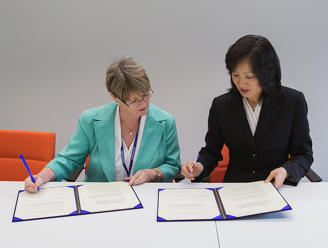 Michelle Lee, at right, signing a memorandum with the director general of IP Australia in September 2014.