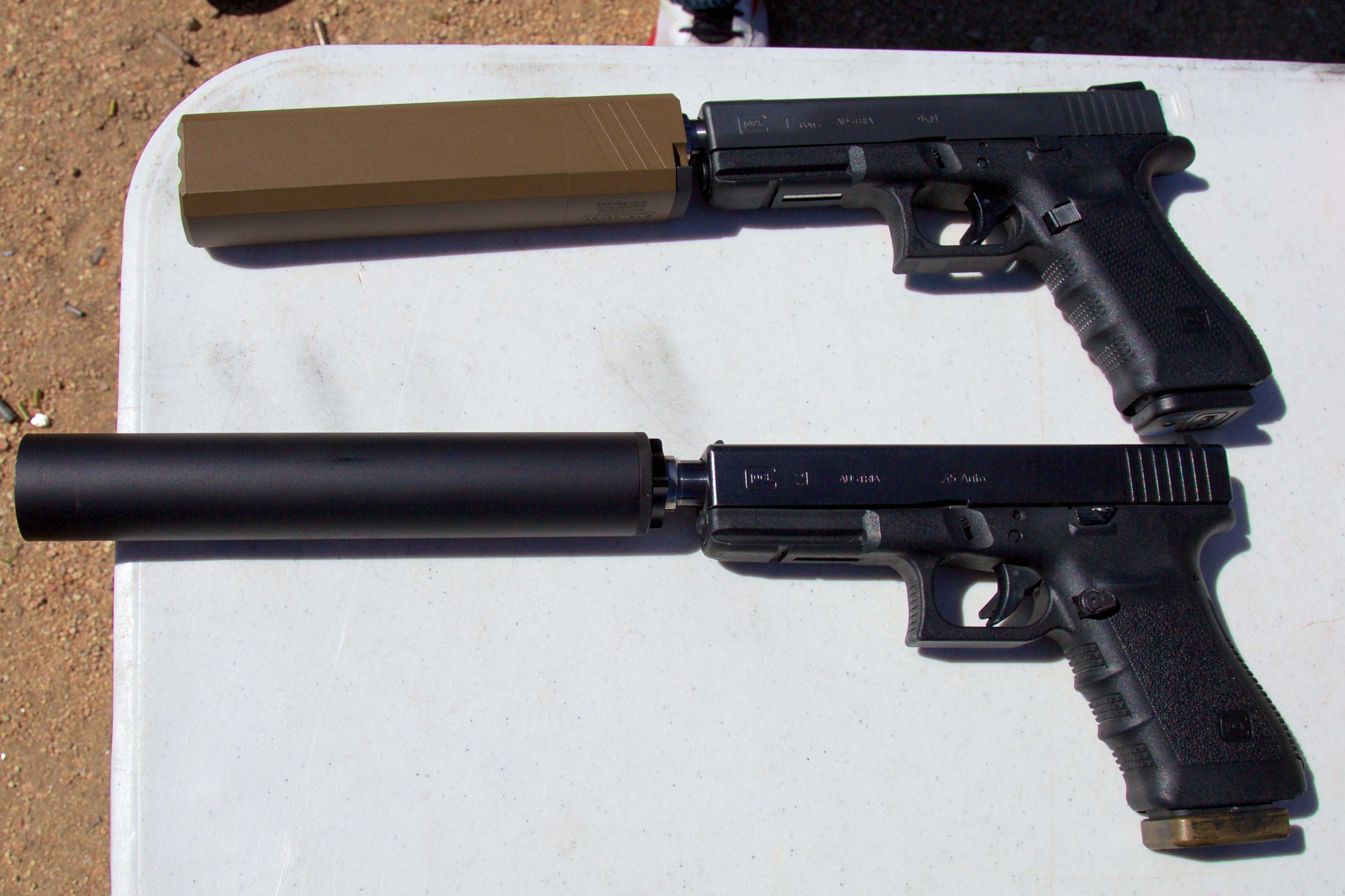 The eccentric Osprey suppressor, top, versus the more traditionally round Octane, bottom. The Osprey's shape keeps it out of the way of the pistol's sights.