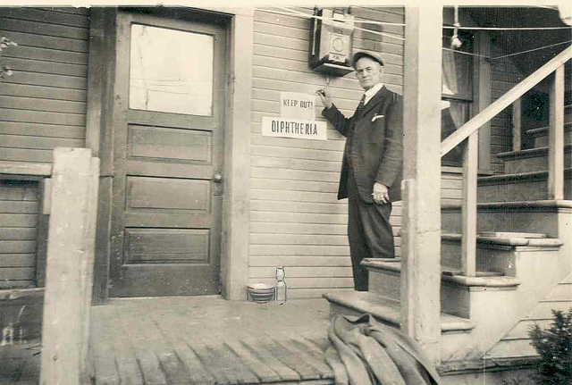 A Washington state health worker places a diphtheria quarantine sign on a house in 1927.