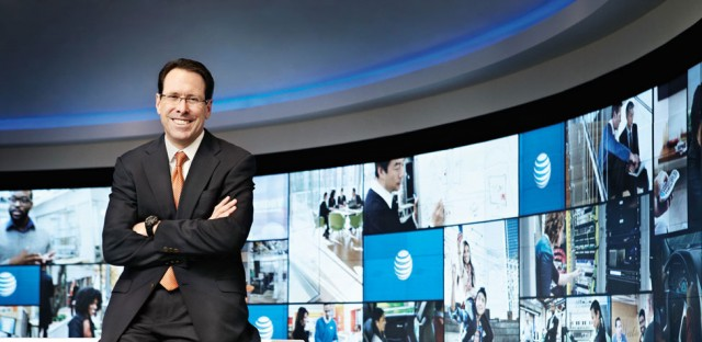 AT&T CEO Randall Stephenson standing with arms crossed in front of a backdrop with AT&T logos.
