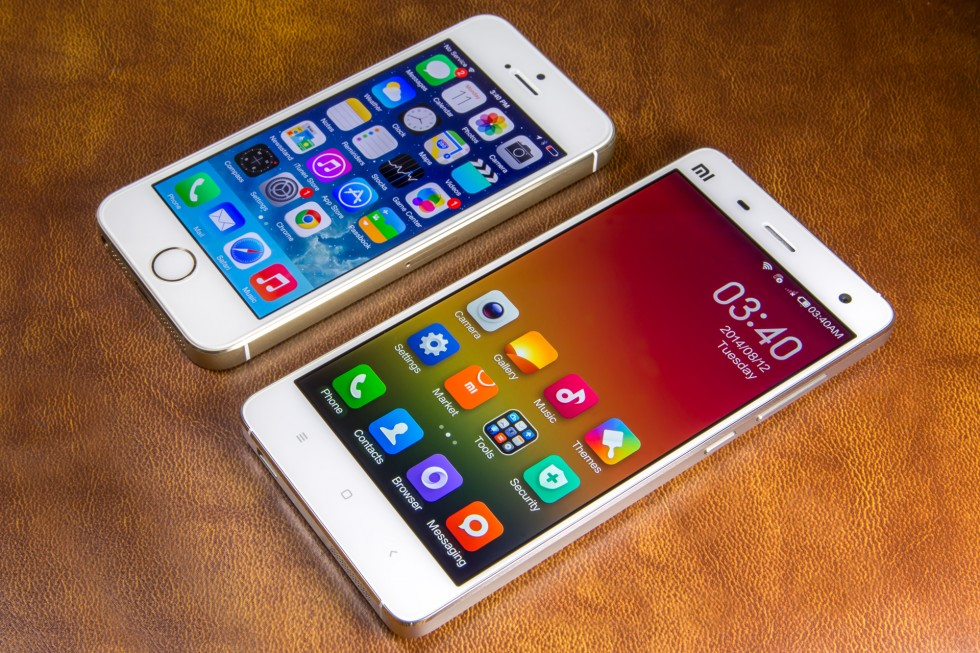 A Xiaomi Mi4 with its inspiration, an iPhone 5s, in the background.