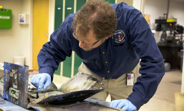 NTSB Materials Engineer Matt Fox examines the casing from the battery involved in the Boston 787 fire.