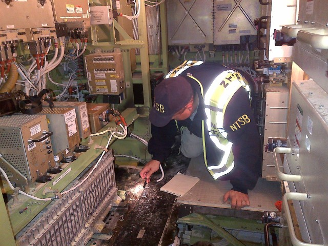NTSB Investigator Mike Bauer inside the aft electronics bay of the JAL Boeing 787 that caught fire at Boston's Logan International Airport in January of 2013.
