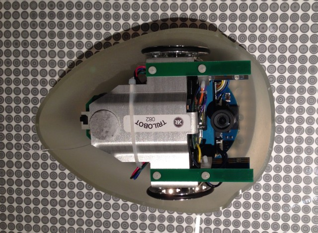The underside of a robot, showing the downward-facing camera. It's sitting on top of an example of a floor grid, showing the distinctive spirals that allow it to figure out its location.