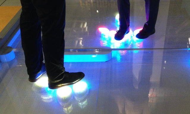 Glowing robots swarm under the feet of some museum-goers.