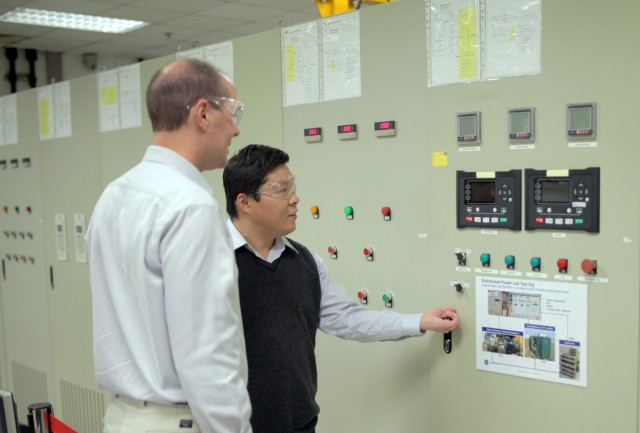 GE's Xu Fu shows the author some of the equipment used to test models of the electric grid.