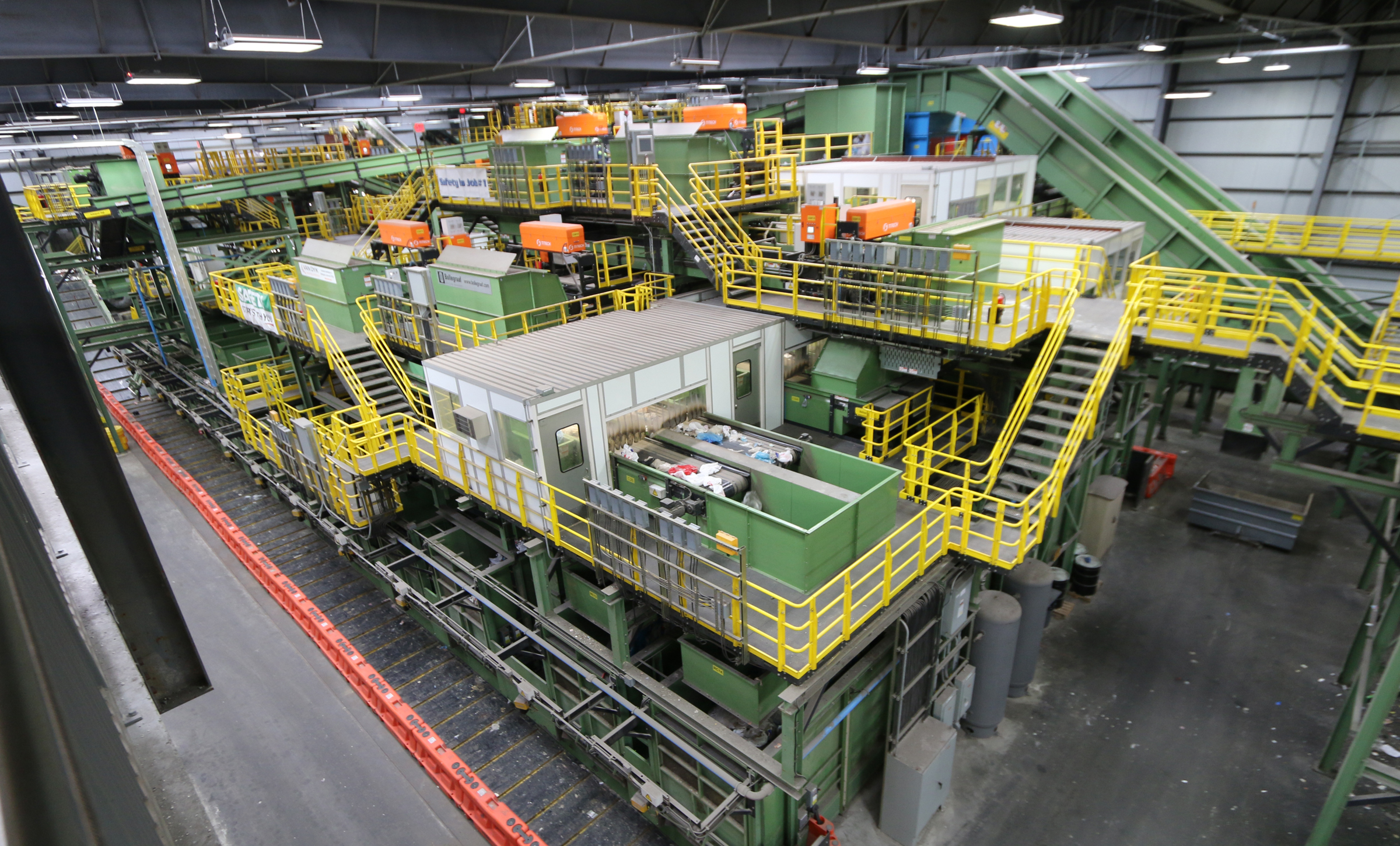 A wide-angle view of the entire New York Sunset Park recycling facility. Lots of individual machinery is tightly clustered around this three-dimensional system of conveyors.